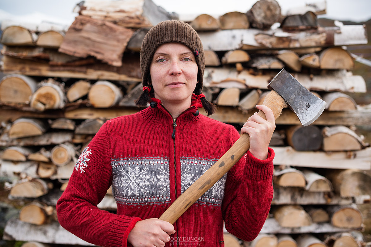 hiker holding axe to cut firewood at mountain hut, Kungsleden trail, Lappland, Sweden