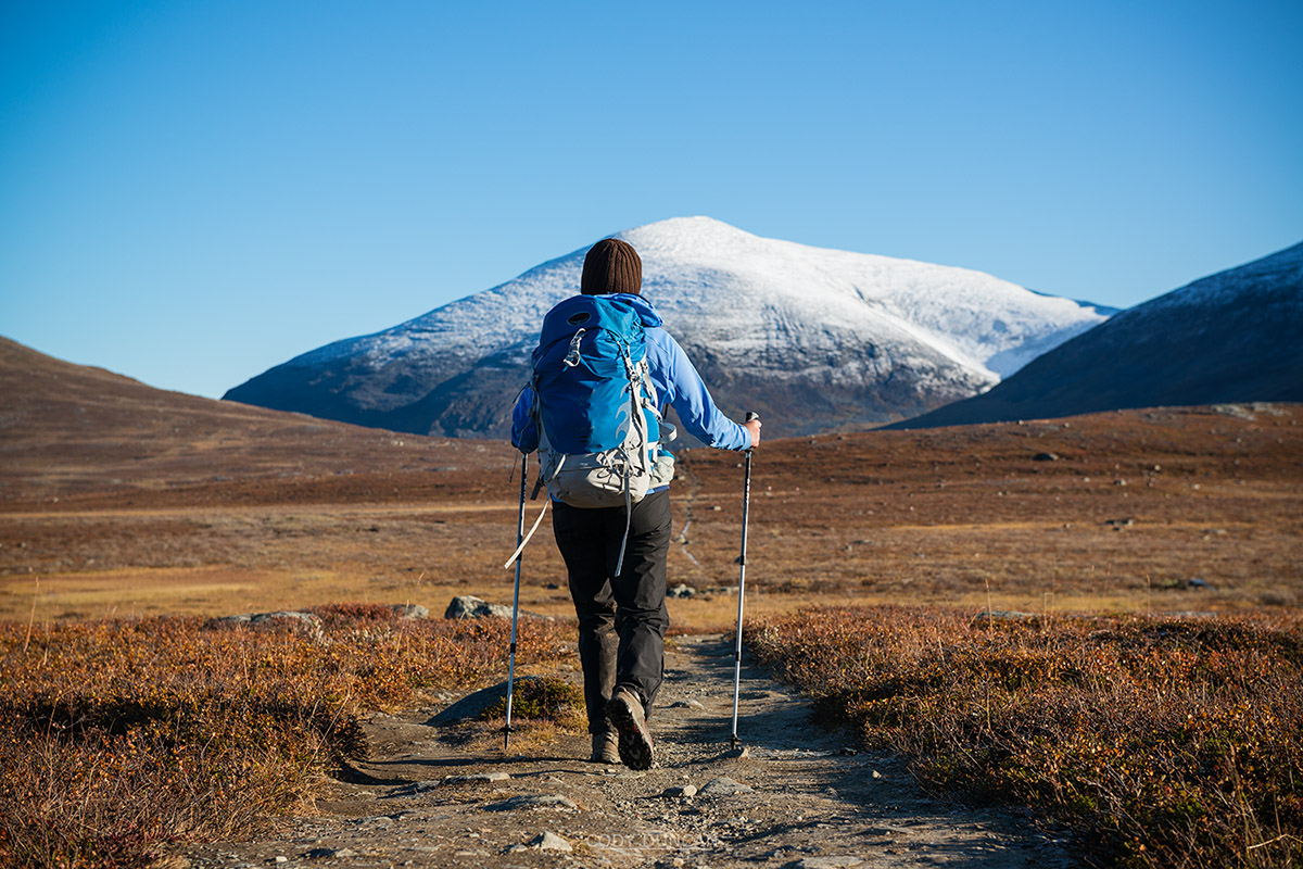 hiking north on Kungsleden trail with snow covered Keron + Giron (1543m) mountain peak in distance, Lappland, Sweden