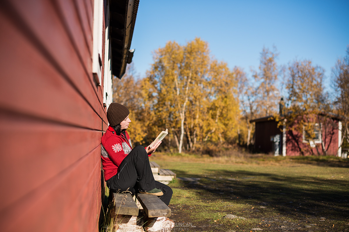 hiker relaxes in sun and reads book outside Abiskojaure mountain hut, Kungsleden trail, Lappland, Sweden
