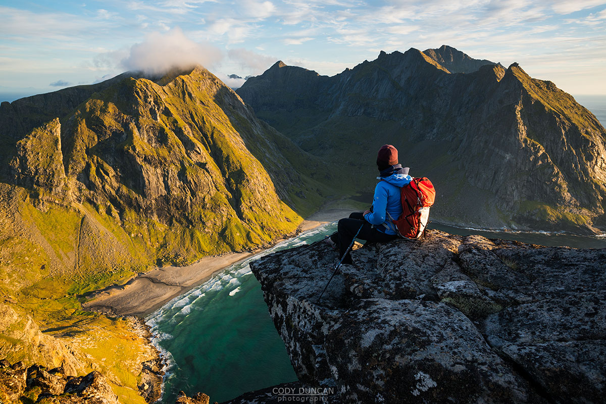 Female hiker enjoying view of Kvalvika beach from near summit of Ryten, Moskenesoy, Lofoten Islands, Norway
